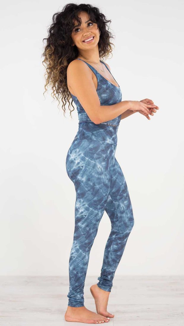 Right side view of model wearing the indigo waves athleisure leggings. they are in a indigo color and have a water waves print in a white and navy color throughout.
