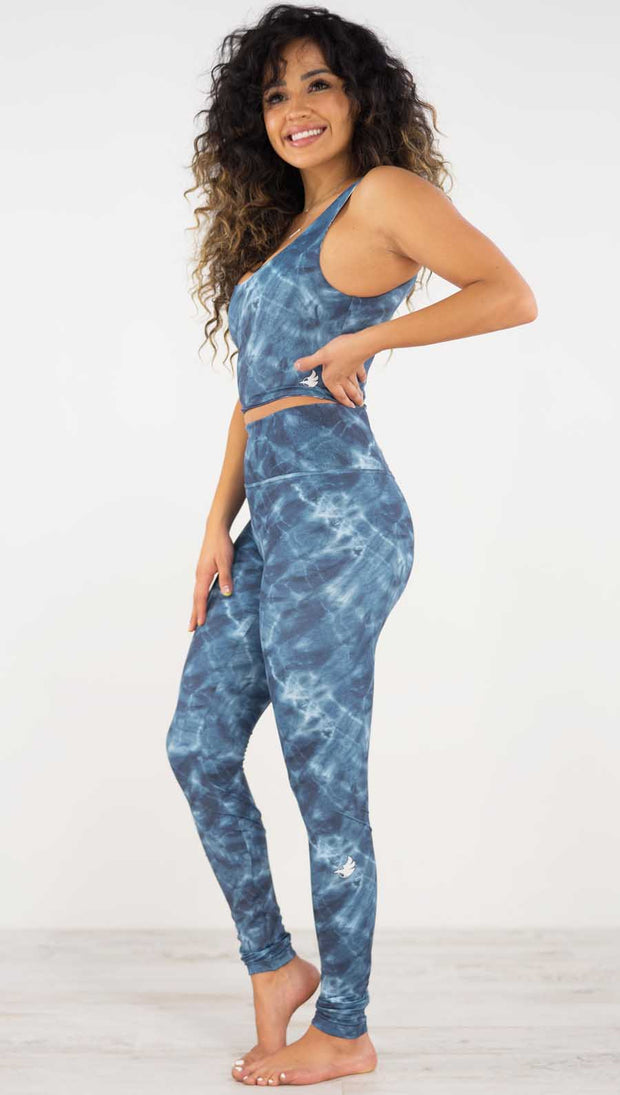 Left side view of model wearing the indigo waves athleisure leggings. They are in a indigo color and have a water waves print in a white and navy color throughout.