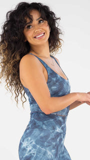 Right side view of model wearing the reversible indigo waves/ spiral crop top. This is the waves side. it is in a indigo color and has a water waves print in a white and navy color throughout the top.