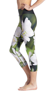 close up left side view of model wearing white jasmine flower themed printed capri leggings