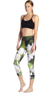 front view of model wearing white jasmine flower themed printed capri leggings