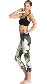 left side view of model wearing white jasmine flower themed printed capri leggings