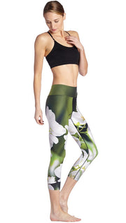 right side view of model wearing white jasmine flower themed printed capri leggings