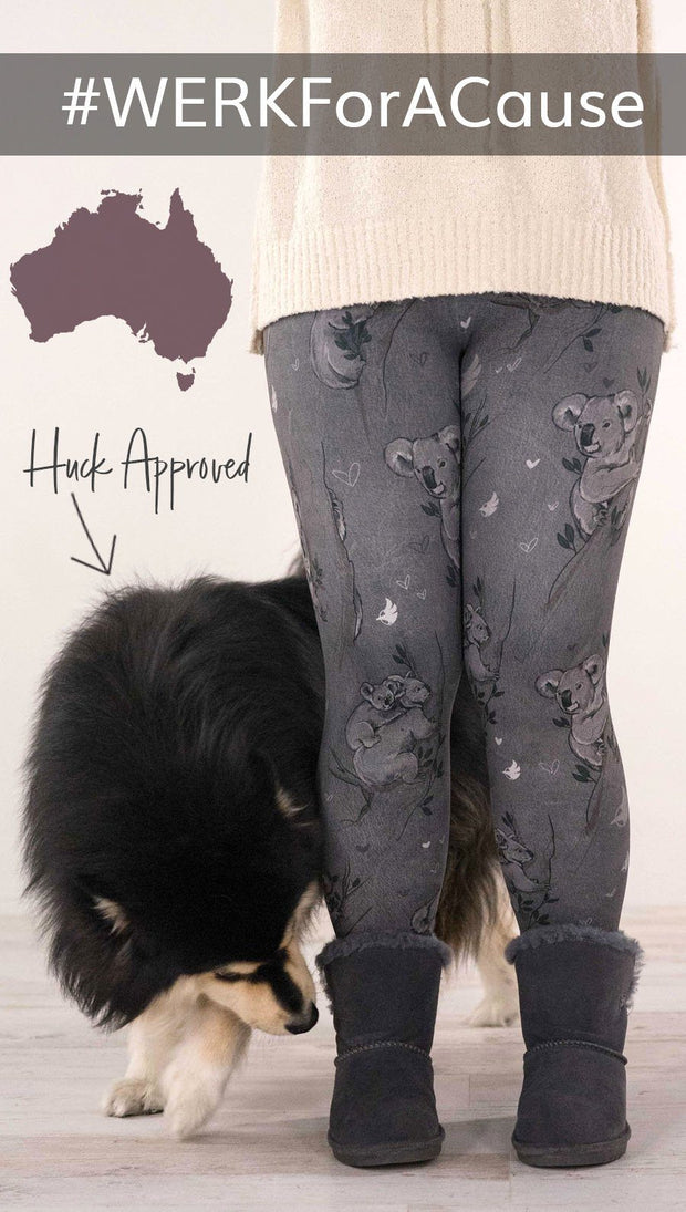 Lower view of model wearing koala printed leggings with tree branches and leaves next to Finnish Lapphund dog
