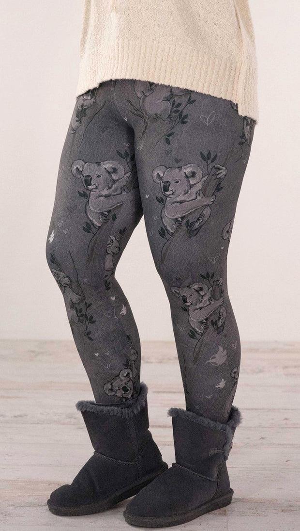 Front view of model wearing koala leggings with branches and leaves