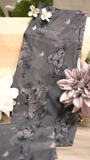 Koala leggings with tree branches and leaves sitting on a table with flowers