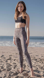 Front view of model wearing koala leggings with tree branches and leaves on the beach