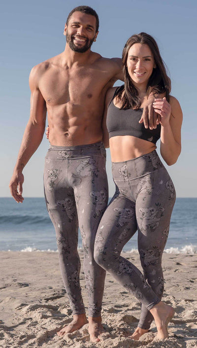 Male and female models standing side by side wearing koala leggings with tree branches and leaves