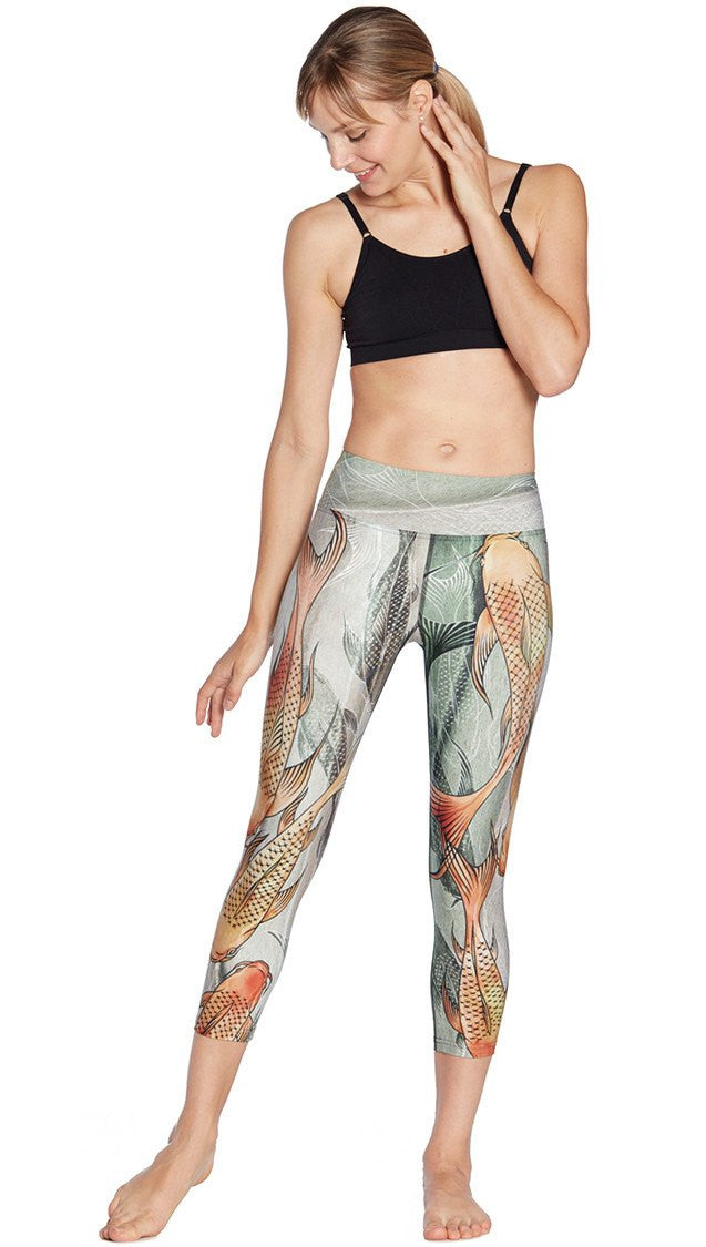 close up right side view of model wearing koi fish themed printed capri leggings