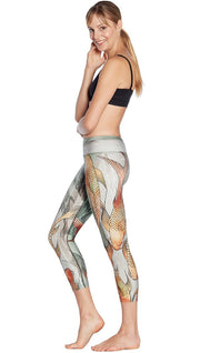 left side view of model wearing koi fish themed printed capri leggings