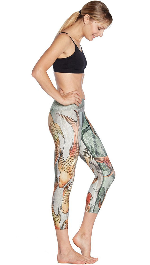 right side view of model wearing koi fish themed printed capri leggings