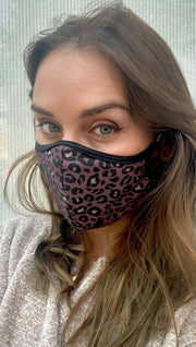 Slightly turned front view of model wearing a purple leopard print mask