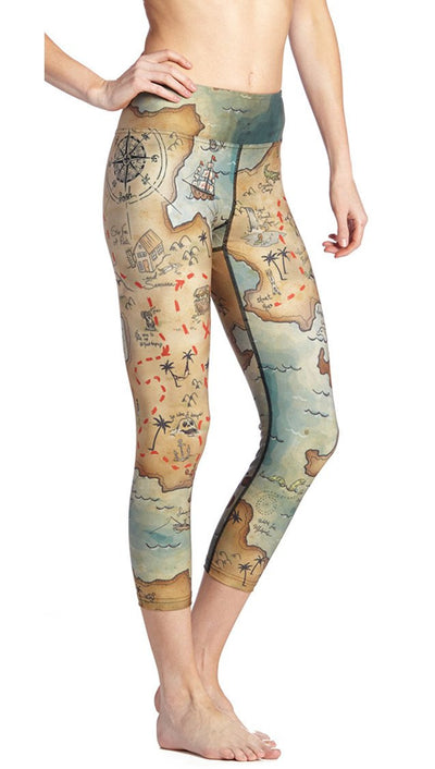 close up side view of treasure map themed printed capri leggings