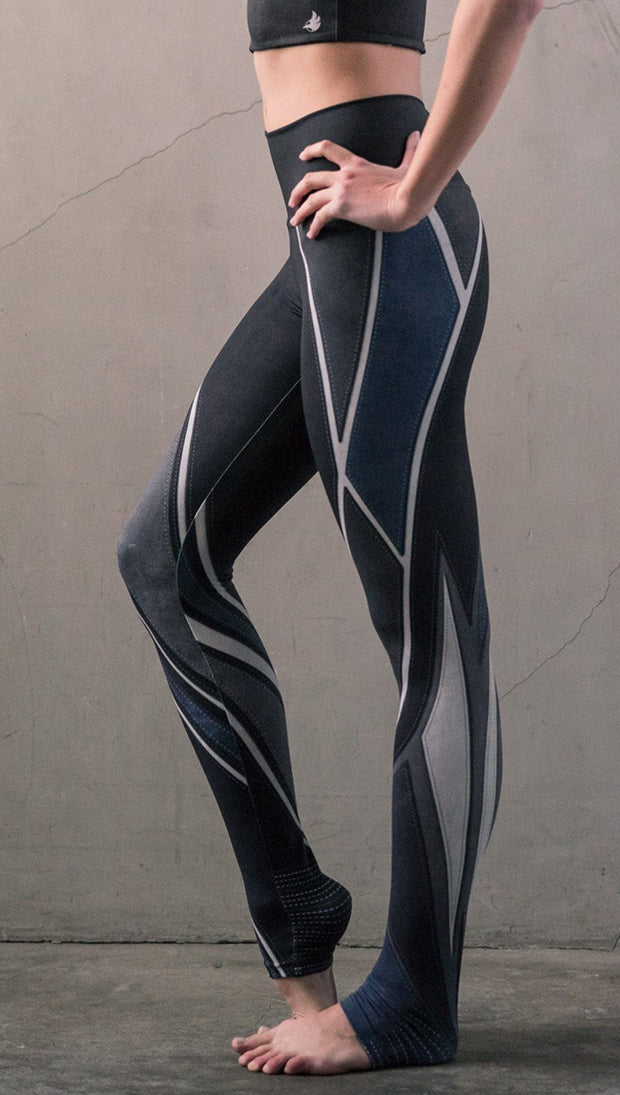 close up left side view of model wearing midnight blue colored motocross inspired printed full length leggings
