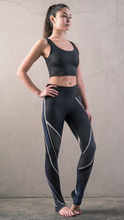 front view of model wearing midnight blue colored motocross inspired printed full length leggings