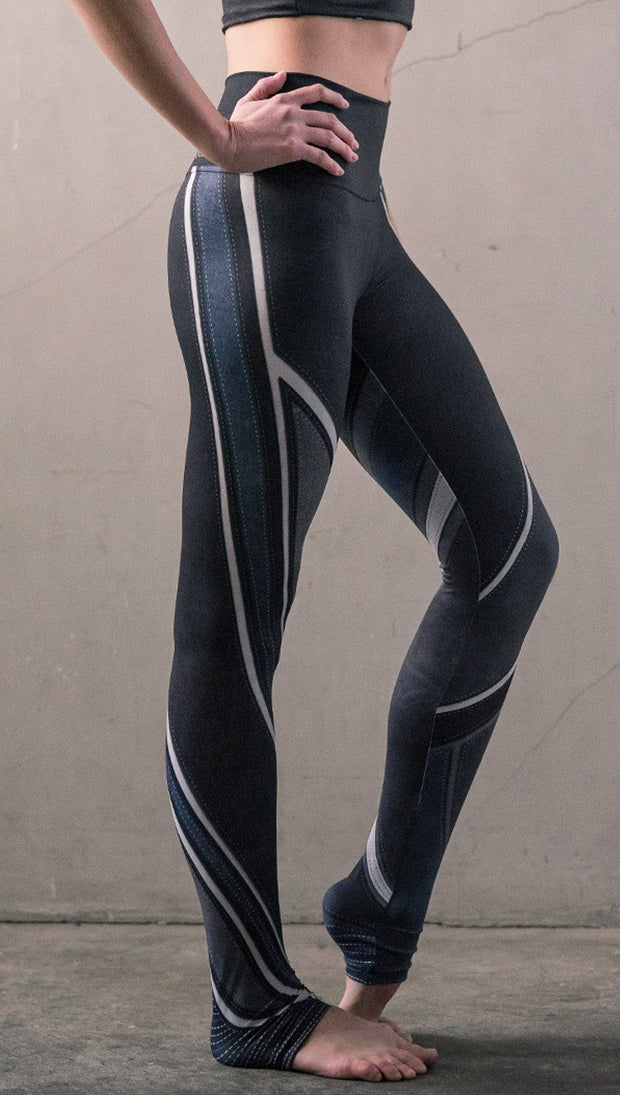 close up right side view of model wearing midnight blue colored motocross inspired printed full length leggings