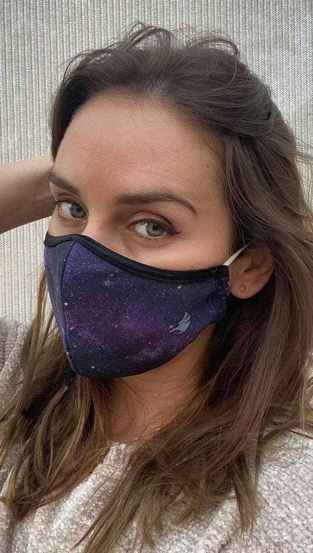 Slightly turned left side view of model wearing a purple mask with tiny white stars and the WERKSHOP logo in the bottom corner