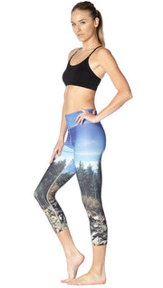 left side view of model wearing New Zealand mountain themed printed capri leggings