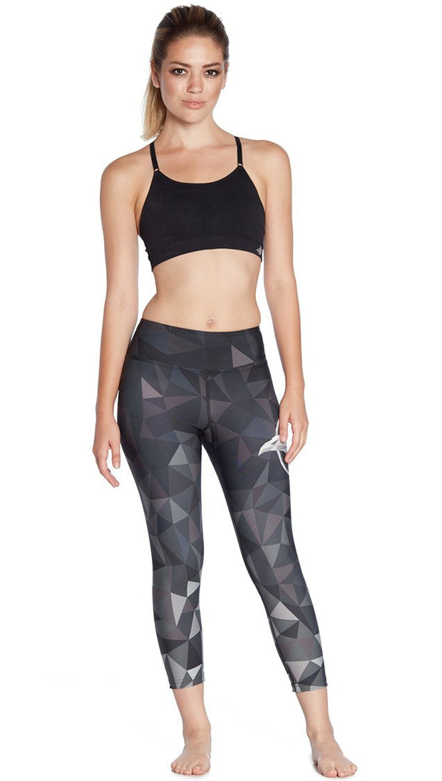 front view of ombre black polygon themed printed capri leggings with large eagle logo motif