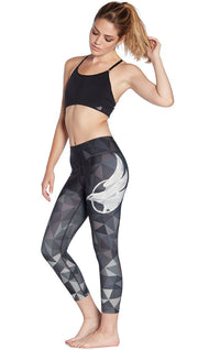 left side view of ombre black polygon themed printed capri leggings with large eagle logo motif