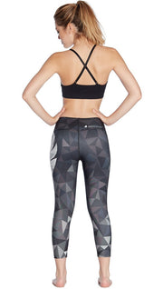 back view of ombre black polygon themed printed capri leggings with large eagle logo motif