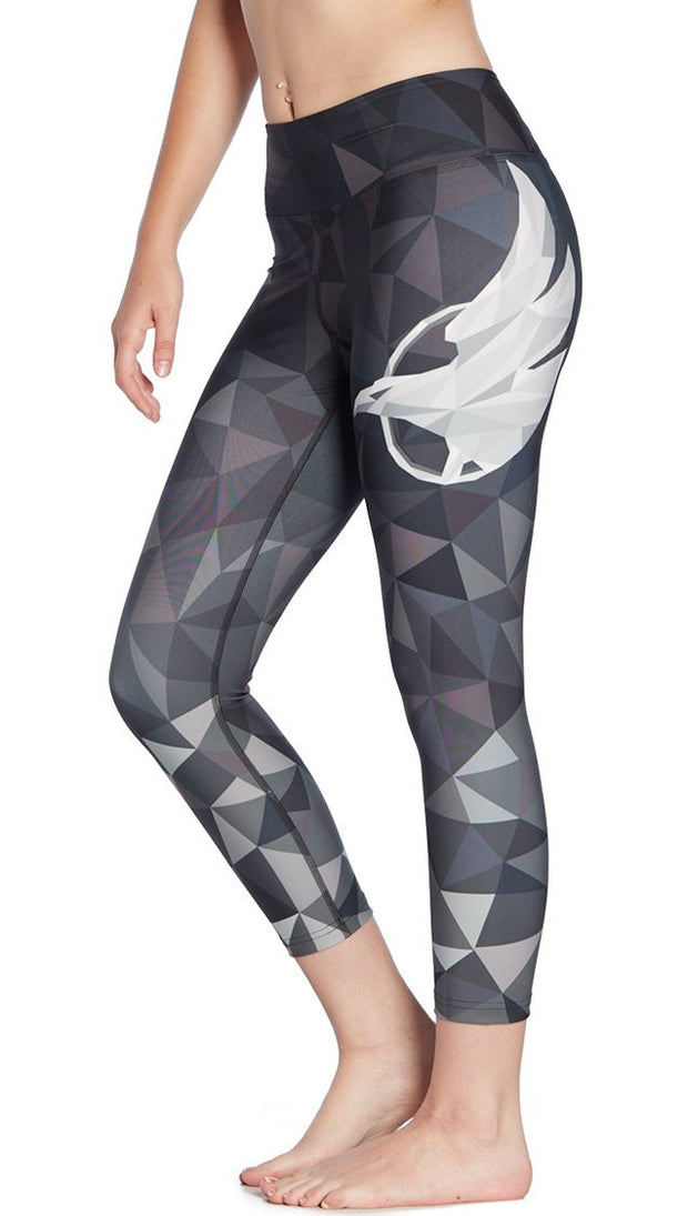 close up left side view of ombre black polygon themed printed capri leggings with large eagle logo motif