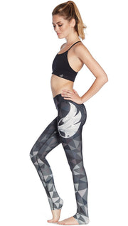 left side view of model wearing ombre black polygon themed printed full length leggings with large eagle logo motif