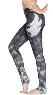 close up left side view of model wearing ombre black polygon themed printed full length leggings with large eagle logo motif