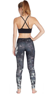 back view of model wearing ombre black polygon themed printed full length leggings with large eagle logo motif