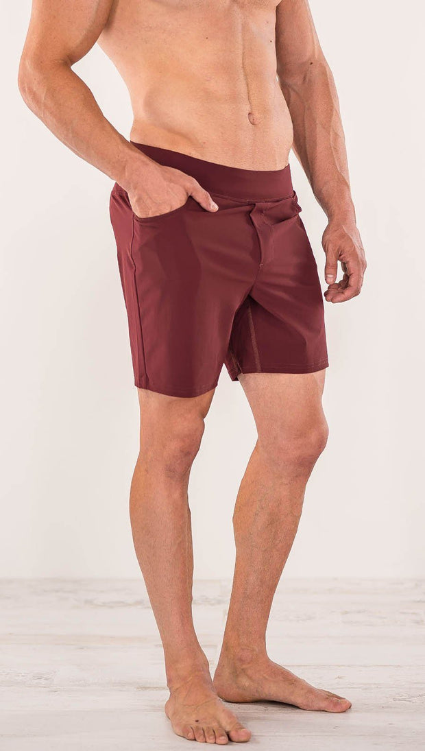 Close up right side view of model wearing men's oxblood performance shorts with slim fit