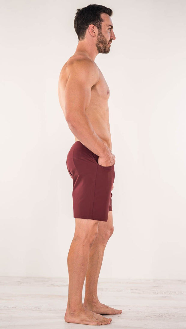 Right side view of model wearing men's oxblood performance shorts with slim fit