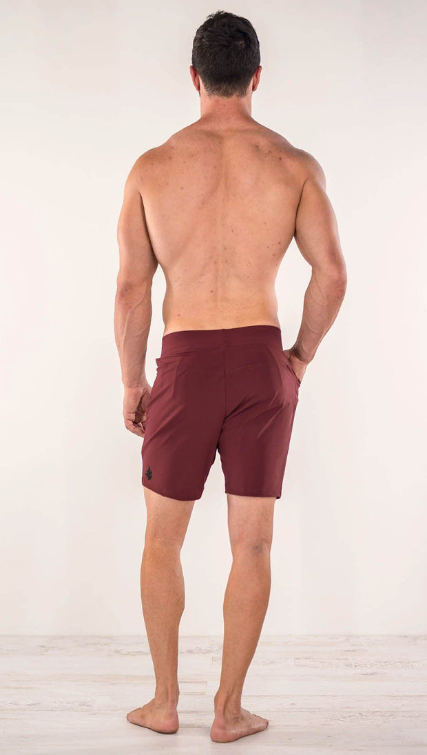 Back side view of model wearing men's oxblood performance shorts with slim fit