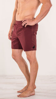 Close up left side view of model wearing men's oxblood performance shorts with slim fit