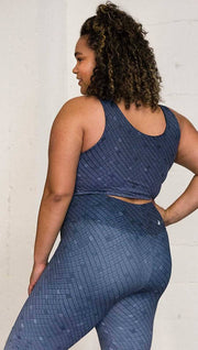 Three quarter length left rear view of a model wearing a blue mosaic tile print reversible crop top with dark gray mosaic tile print on the other side