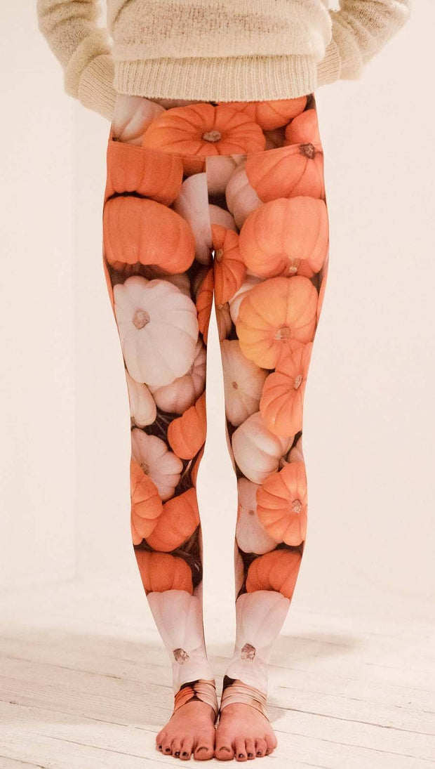 Front view of model wearing white and orange pumpkin leggings