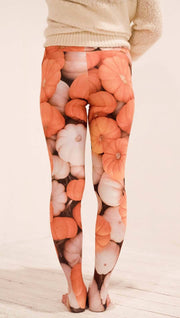 Back view of model wearing white and orange pumpkin leggings