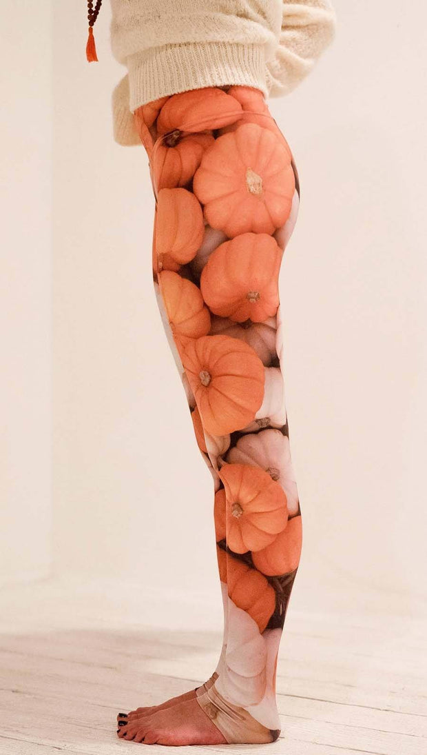 Left side view of model wearing white and orange pumpkin leggings