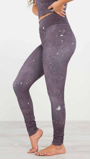 Left side view of model wearing purple high rise athleisure leggings with light gray splatter spots throughout