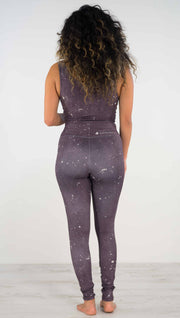 Back view of model wearing purple high rise athleisure leggings with light gray splatter spots throughout