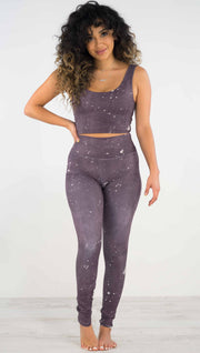 Front view of model wearing purple high rise athleisure leggings with light gray splatter spots throughout