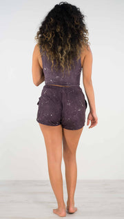Back view of model wearing purple mid rise shorts with light gray splatter spots throughout
