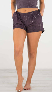 Front view of model wearing purple mid rise shorts with light gray splatter spots throughout and a pocket on each side