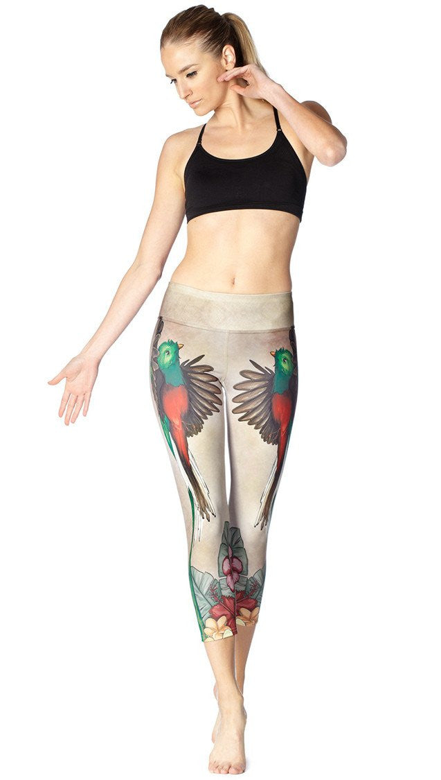 close up front view of model wearing quetzal bird themed printed capri leggings