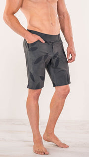 Close up diagonally left side view of model wearing gray printed performance shorts with slim fit and vilva leaf inspired art