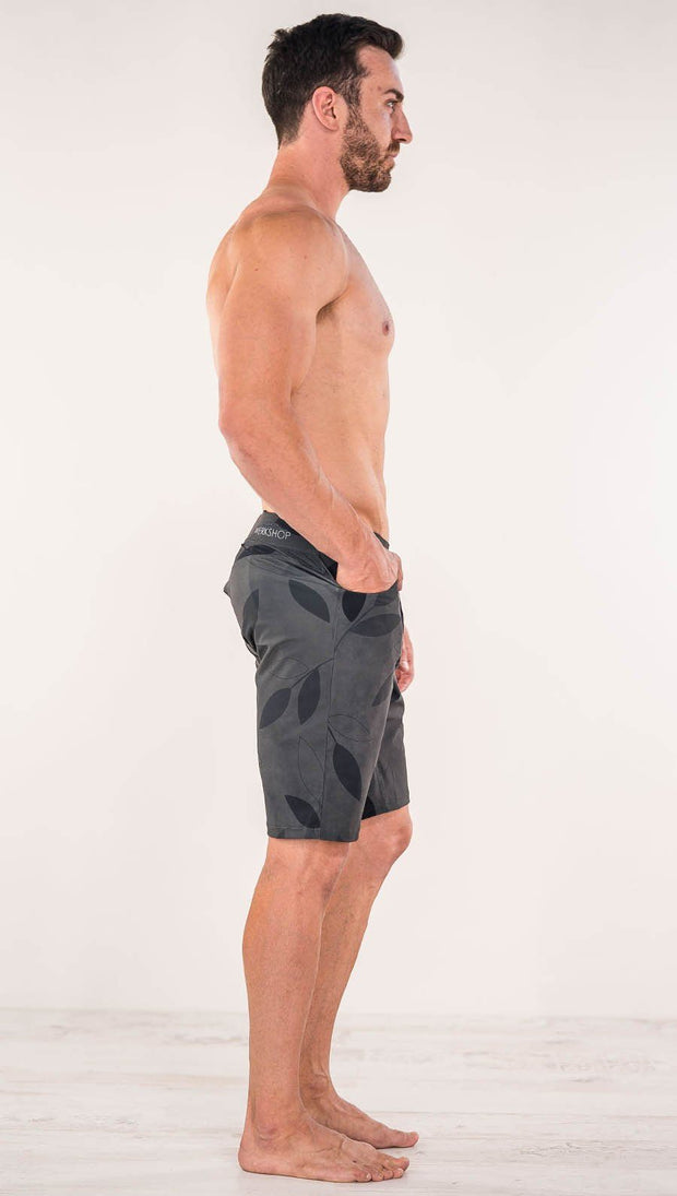 Right side view of model wearing gray printed performance shorts with slim fit and vilva leaf inspired art