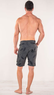 Back side view of model wearing gray printed performance shorts with slim fit and vilva leaf inspired art