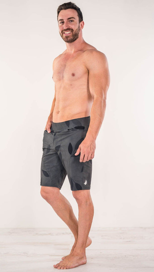 Diagonally left side view of model wearing gray printed performance shorts with slim fit and vilva leaf inspired art