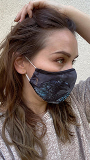 girl wearing mask with gothic-inspired blue raven printed on one side and blue feathers on the opposite side.