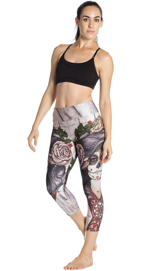 front view of model wearing sugar skull themed printed capri leggings