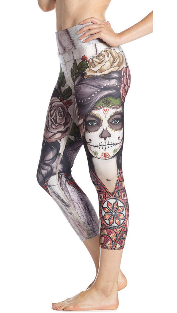 close up left side view of model wearing sugar skull themed printed capri leggings